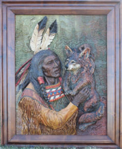 Wood Carving of a Native American holding a Wolf Pup